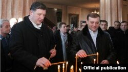 Мэр Еревана Тарон Маркарян и мэр Тбилиси Георгий Угулава зажигают свечи в церкви Сурб Эчмиадзин в Тбилиси,15 декабря 2013 г.