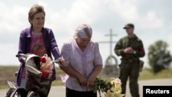 Женщины с цветами у места падения обломков самолета компании Malaysia Airlines в годовщину трагедии. Село Грабово Донецкой области, 17 июля 2015 года.