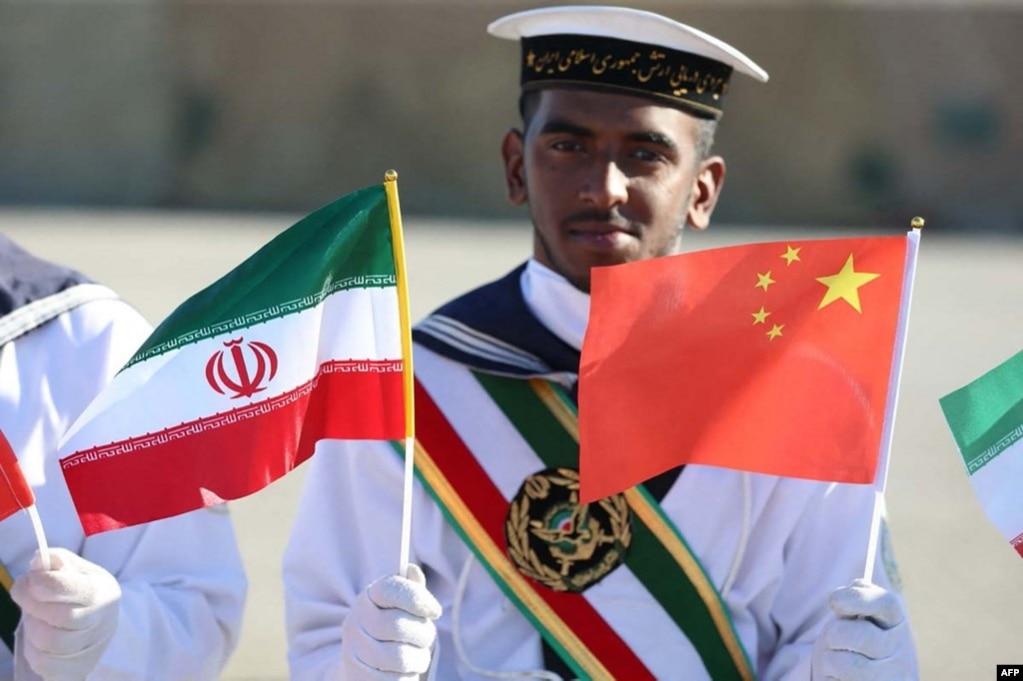 Иранский военный моряк держит флаги КНР и своей страны. Совместные военно-морские учения Китая и Ирана. Декабрь 2019 года