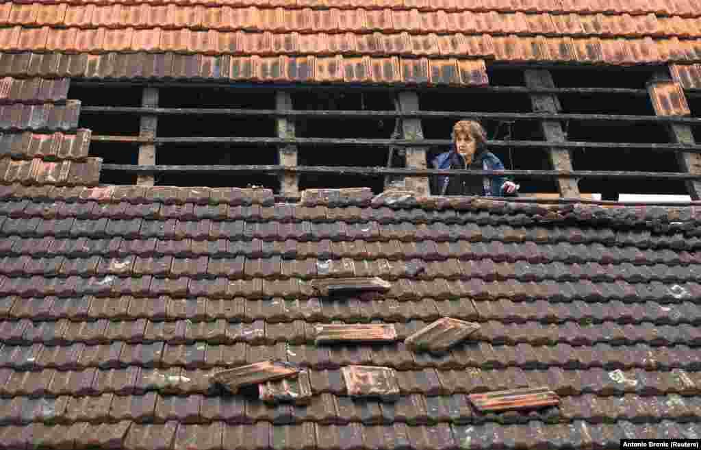 Жінка на даху пошкодженого будинку після землетрусу магнітудою 5,2 у селі Брест- Покупський. Хорватія, 28 грудня 2020 року