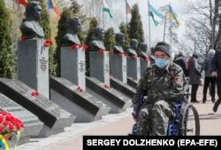 """Kiev: unul din foștii """"lichidatori"""" de la Cernobîl în fața monumentului ridicat în memoria celor care au participat la efortul de curățare a locului accidentului nuclear, Ucraina, 26 aprilie 2021."""