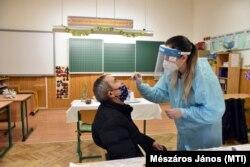 A Semmelweis Egyetem koronavírus-tesztet végző szülésznő hallgatója mintát vesz egy pedagógustól.