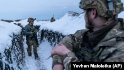 Ukrainian servicemen walk along a snow-covered trench at the front line near Vodiane in eastern Ukraine on March 5.