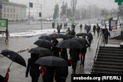 """Минск шаарындагы """"Галерея"""" соода борборунун жанынан кара кол чатырга кызыл тасма таккан кара кийимчен аялдар басып өтүштү. Бул - өлкөдөгү саясий туткундарды колдоо иш-чарасы болду. Беларус. 2021-жылдын 12-марты."""
