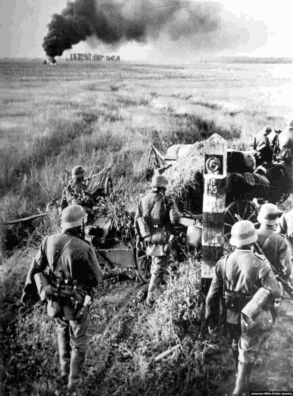 Это фото - немецкие солдаты, проносящие пушку мимо советского пограничного знака - одно из первых изображений, сделанных во время операции Барбаросса, нападения на Советский Союз, которое началось на рассвете 22 июня 1941 года.