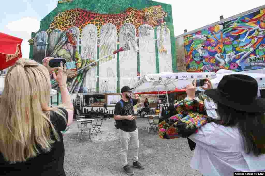 """Valentin Dobrin oferă turiștilor explicații în cadrul evenimentului """"Alternative Bucharest Tour"""". În cadrul turului sunt explorate zonele de artă stradală, picturile murale, graffiti și arhitectura din București."""