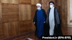 Outgoing President Hassan Rohani (left) and President-elect Ebrahim Raisi meet in Tehran on June 23.