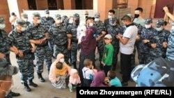 Баглан Орынбеков с женой и детьми в полицейском кольце. Нур-Султан, 25 мая 2021 года.