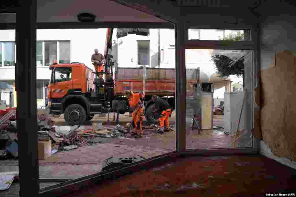 Коммунальные работники убирают завалы и мусор с улицы после сильного наводнения в Ойскирхене, западная Германия, 18 июля 2021 года
