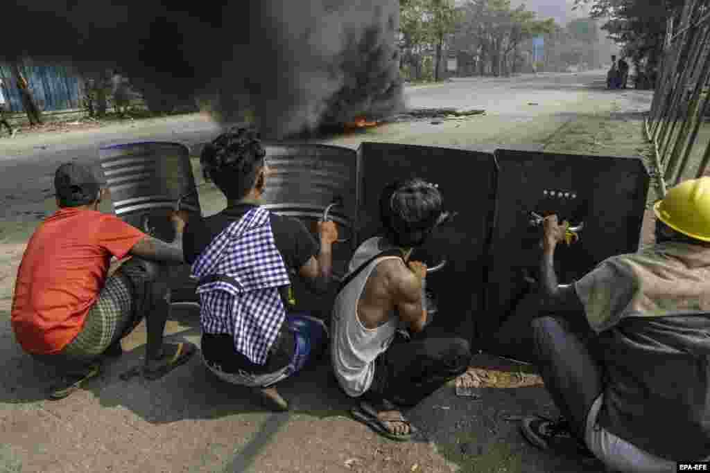 Демонстранттар Янгон шаарынын чет жакасындагы Хлаингтая (Хлаинг Тхаряр) шаарчасында темир калкандарга жашырынып турушат. Бирма. 2021-жылдын 14-марты.