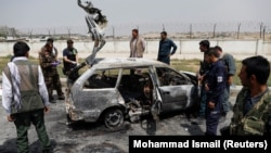 Afghan officials inspect a vehicle from which insurgents fired rockets in a deadly attack in Kabul on August 18.
