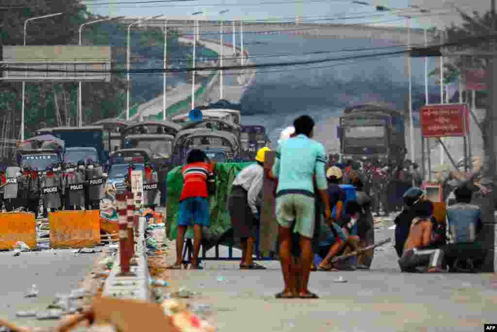 Протестувальники ховаються від поліції за саморобними щитами під час розгону демонстрацій проти військового перевороту. Район Хлаінг Тар'яр міста Янгону, М'янма, 14 березня 2021 року
