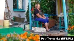 Калачи ауылының тұрғыны Татьяна Шумилина үйінің ауласында отыр. Ақмола облысы, 29 шілде 2020 жыл.
