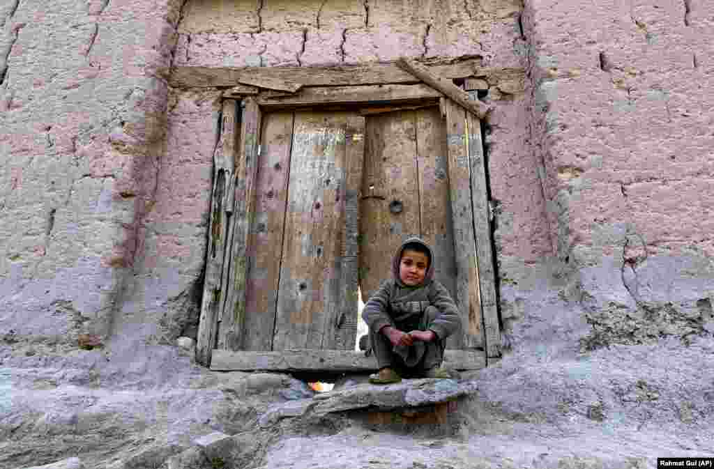 An Afghan boy sits in front of his home on the outskirts of the city of Jalalabad. (AP/Rahmat Gul)