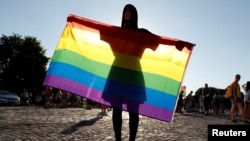 A demonstrator holds a rainbow flag at a rally in Budapest protesting against a law that bans LGBT content and materials in schools. (file photo)