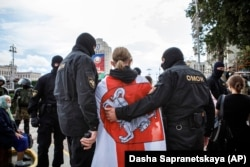 Riot police detain a protester, draped in an old Belarusian national flag, on Independence Square in Minsk late last month.