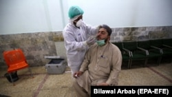 A health official conducts a COVID-19 test on a journalist in Peshawar on June 3.