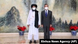 Taliban co-founder Mullah Abdul Ghani Baradar (left) and Chinese Foreign Minister Wang Yi pose for a photo during their meeting in Tianjin in July.