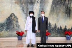 Taliban co-founder Mullah Abdul Ghani Baradar (left) and Chinese Foreign Minister Wang Yi pose for a photo in Tianjin on July 28.