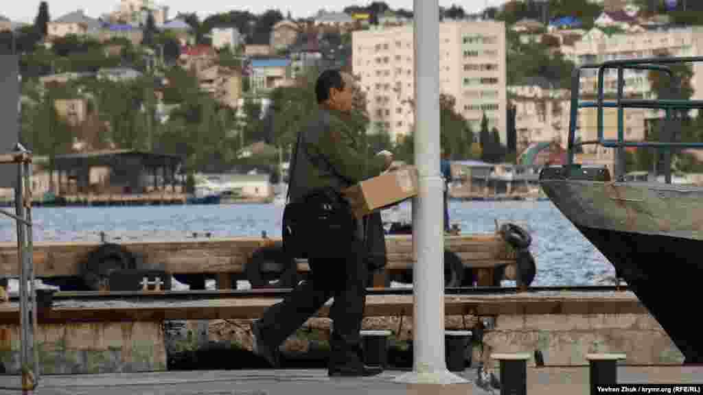 Перед посадкой на катер мужчина берет медицинскую маску из коробки. Российские власти Севастополя заявляют, что на прошлой неделе бесплатно раздали в общественном транспорте 175 тысяч масок