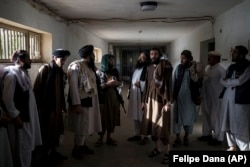 Taliban fighters, some of them former prisoners, chat in an empty area of the Pul-e Charkhi Prison in Kabul on September 13.