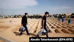 Iranian men walk past empty, prepared graves at Behesht Zahra, Tehran's main cemetery.