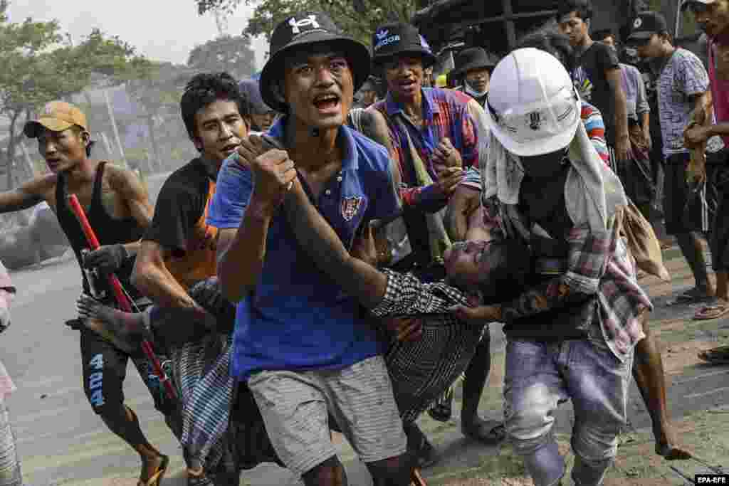 An injured demonstrator is carried to receive medical attention during a protest against the military coup in Hlaingthaya (Hlaing Tharyar) Township, outskirts of Yangon, Myanmar, 14 March 2021.