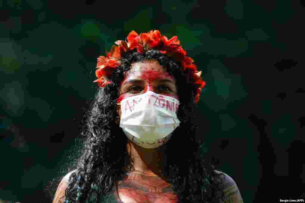 Őslakos nő tüntet Bolsonaro tervezete ellen, amely legalizálná földjeiken az aranybányászatot. A brazil elnök egy beszédében azt mondta, az őslakos területek akadályozhatják az ország fejlődését