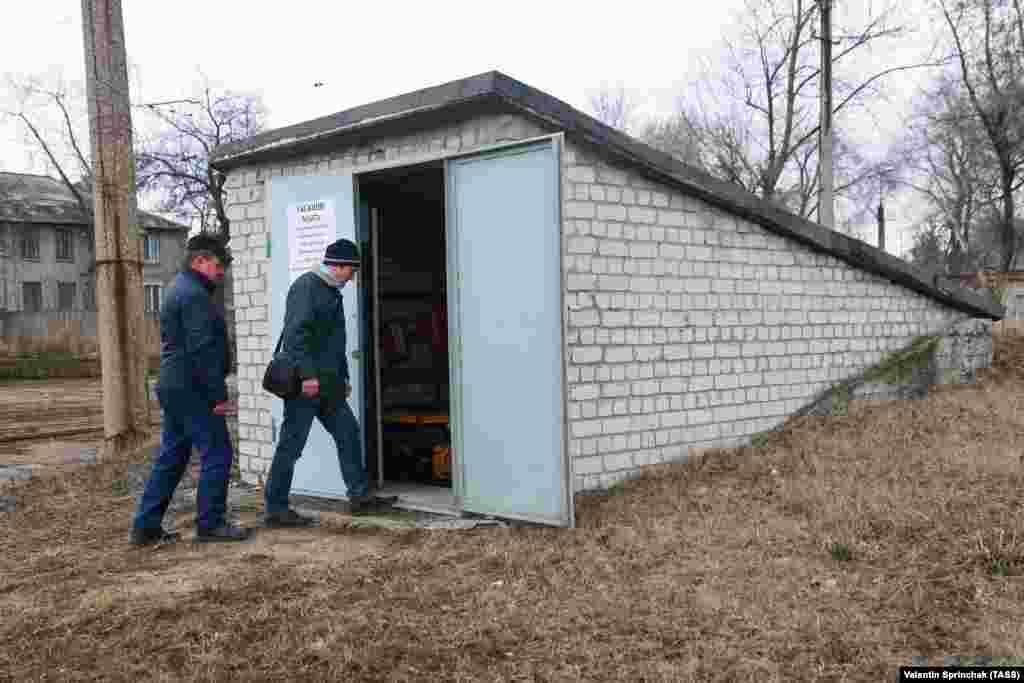 Мужчины заходят в бомбоубежище на территории трамвайного депо в Донецкой области. 24 марта 2021 года. Эта зона контролируется сепаратистами.