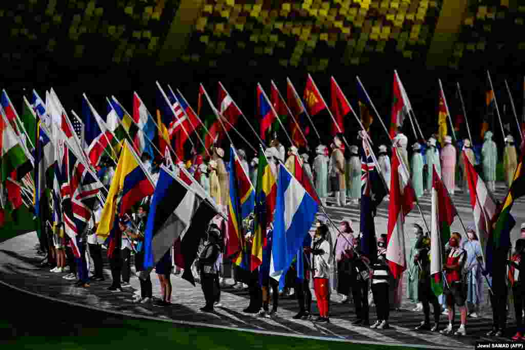 Athletes delegations pose with their national flag as they enter during the closing ceremony of the Tokyo 2020 Olympic Games, at the Olympic Stadium, in Tokyo, on August 8, 2021.