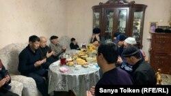 Родственники жертв Жанаозенских событий 2011 года за столом читают молитву в память о погибших. Жанаозен, 16 декабря 2020 года.
