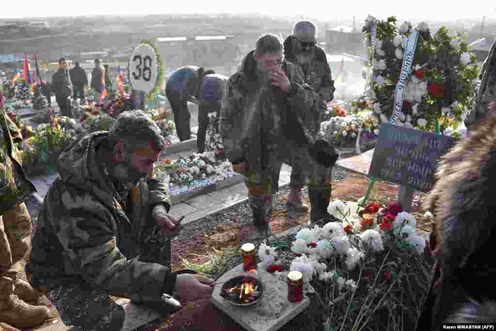 Men in military uniform at Yerablur cemetery on December 19 at the grave of a volunteer who died in the conflict