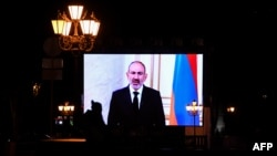ARMENIA -- A woman walks in front of a big screen displaying a footage with Armenian Prime Minister Nikol Pashinian in Yerevan, October 5, 2020