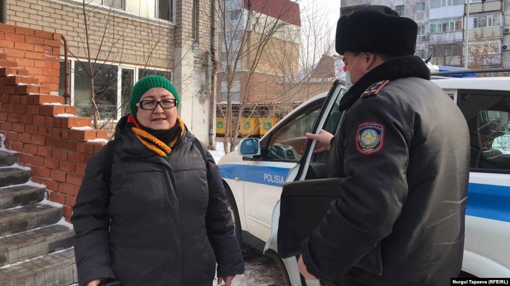 Независимый журналист и блогер Айгуль Утепова и сотрудник полиции рядом со служебным автомобилем. Нур-Султан, 23 ноября 2020 года.