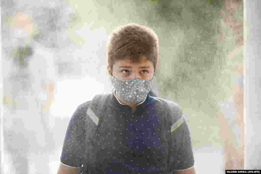 An elementary-school student wearing a face mask passes through a disinfection tunnel on the first day of school in Pristina. ​Kosovo's government postponed the start of the school year for two weeks due to the COVID-19 pandemic.