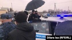 Арнайы жасақ наразы әйелді полиция көлігіне күштеп отырғызып жатыр. Алтынтөбе ауылы, Шымкент, 4 сәуір, 2021 жыл.