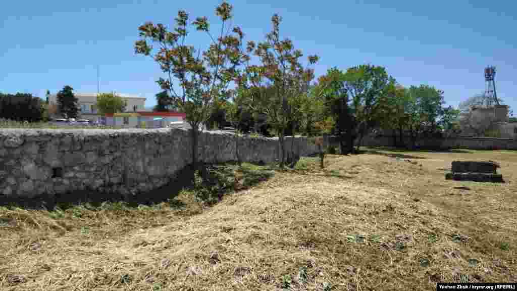 У забора, разделяющего караимское и еврейское кладбища – несколько глубоких, заросших травой ям. Кто, когда и для какой цели их вырыл, неизвестно. А кладбища разделяет даже не проход – пролом в стене