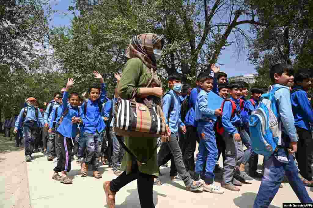 Несмотря на риски, некоторые школы открылись вновь. Эти идущие в класс ученики средней школы и их учительница сфотографированы в Кабуле 30 августа