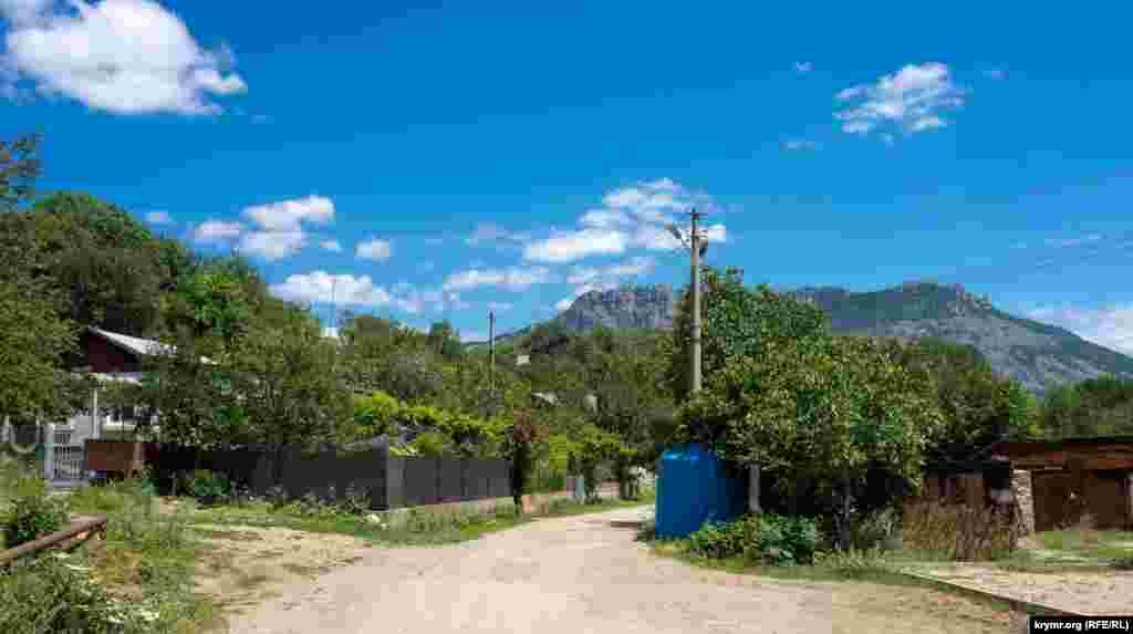 Yuqarı Şumanıñ azbar bağçalarınıñ yeşilligine dalğan Simferopolskoye şosse soqağı ormandan Aqmescit-Yalta yoluna çıqa