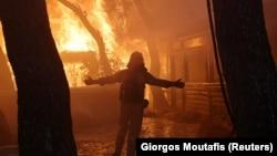 Пожарникар во предградието Варимпомпи, северно од Атина, Грција, 3 август 2021 година