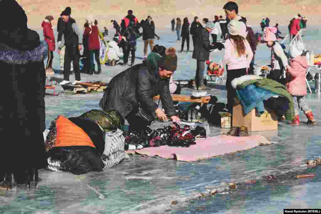 Часть озера заняли местные жители. Они зарабатывают на прокате коньков и самодельных санок.
