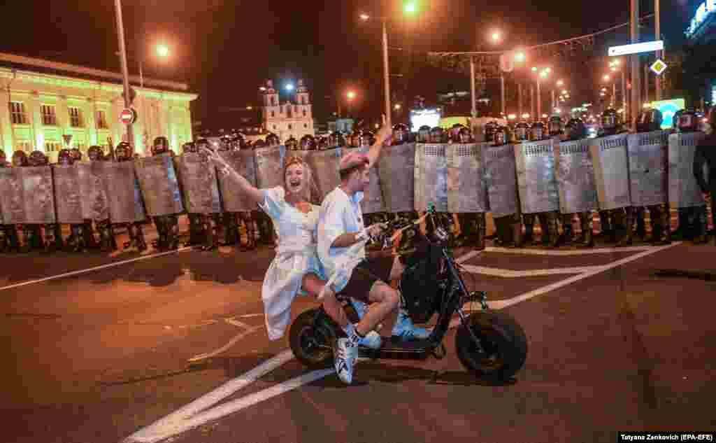 Protesters ride an electric bike in front of police during a protest after polling stations closed at the presidential election in Minsk on August 9. (epa-EFE/Tatyana Zenkovich)