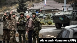 NAGORNO-KARABAKH -- Russian peacekeepers (R and 3rdR) stop a car at their checkpoint outside the city of Stepanakert, November 13, 2020
