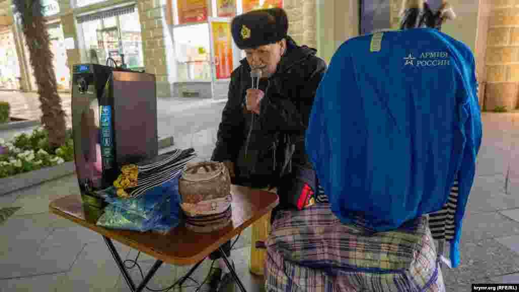 А пенсіонер у норковій шапці з військово-морською кокардою співає як уміє радянські пісні та заодно продає морські пілотки