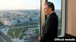 Өзбекстан президенті Шавкат Мирзияев Ташкенттегі Конгресс-холл ғимаратынан сыртқа қарап тұр.