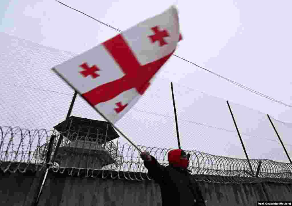 Pristalice opozicionara Nike Melie mašu zastavom Gruzije na protestu 24. februara zahtevajući njegovo puštanje iz zatvora u gradu Rustavi (Reuters/Irakli Gedenidze)