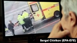 A person watches a video on social media showing Russian opposition leader Aleksei Navalny being carried on a stretcher by an ambulance team in Omsk on August 20.