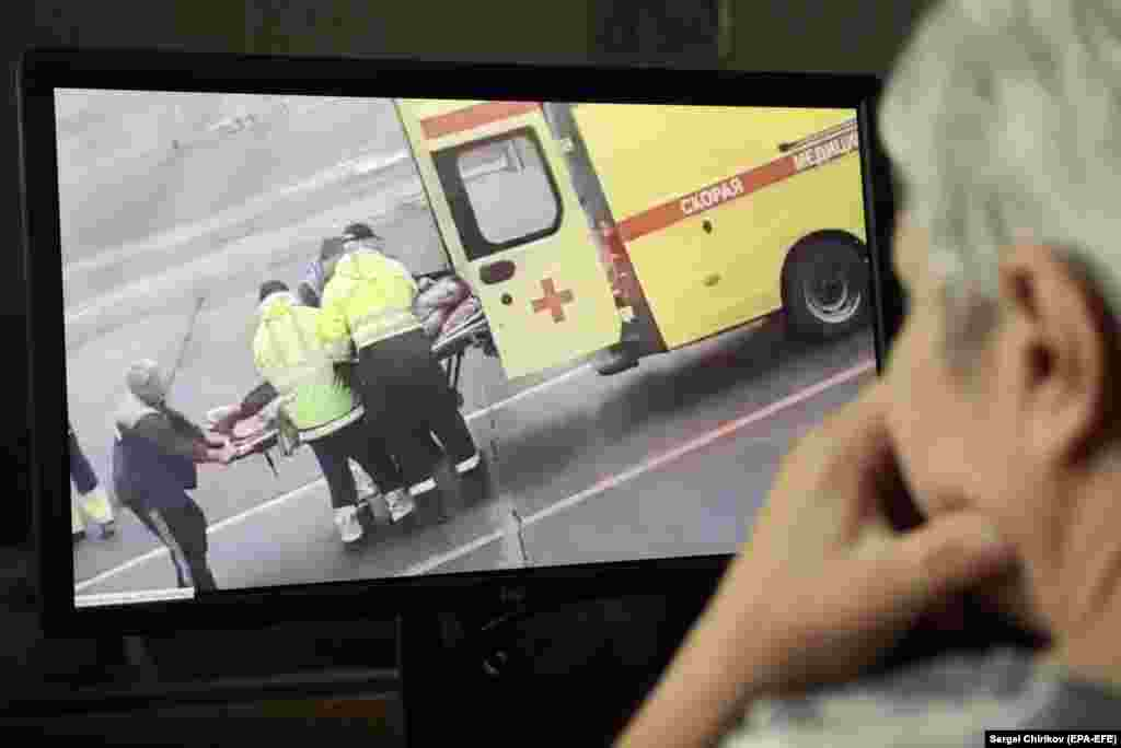 A person watches a video on social media showing Navalny being carried on a stretcher by an ambulance team in Omsk after falling gravely ill from suspected poisoning while aboard a flight from Tomsk to Moscow on August 20.