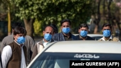 Drivers who work for a Pakistan-based Chinese company look on as they wear protective face masks before their temperatures are checked in Islamabad on January 30.