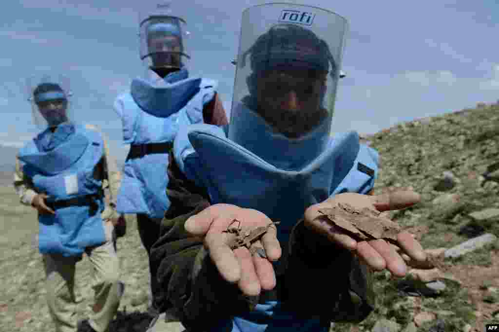 A sapper displays pieces of land mines in the village of Sangaw on the outskirts of Kabul. (AFP/Shah Marai)